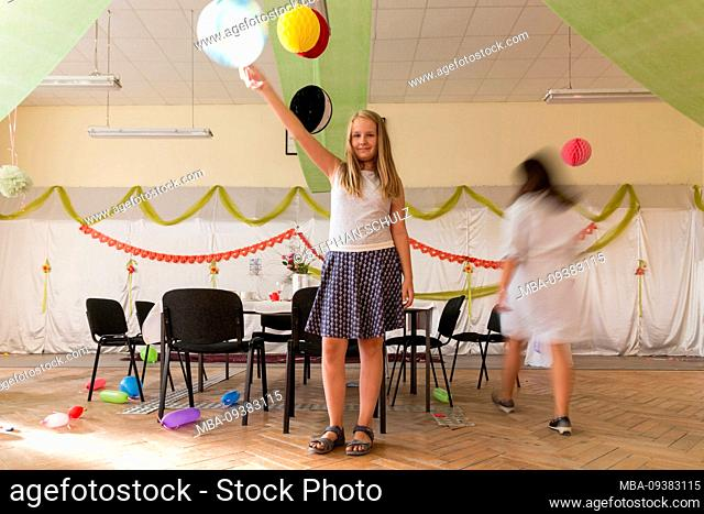 A girl holds a balloon in the air while other party guests clean up or are already gone