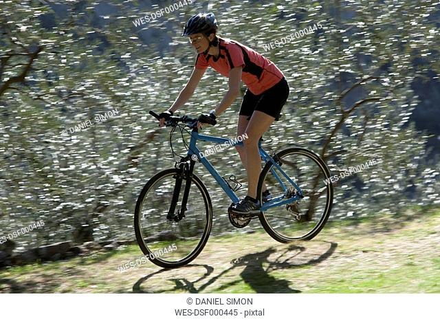 Italy, Mid adult woman riding bicycle