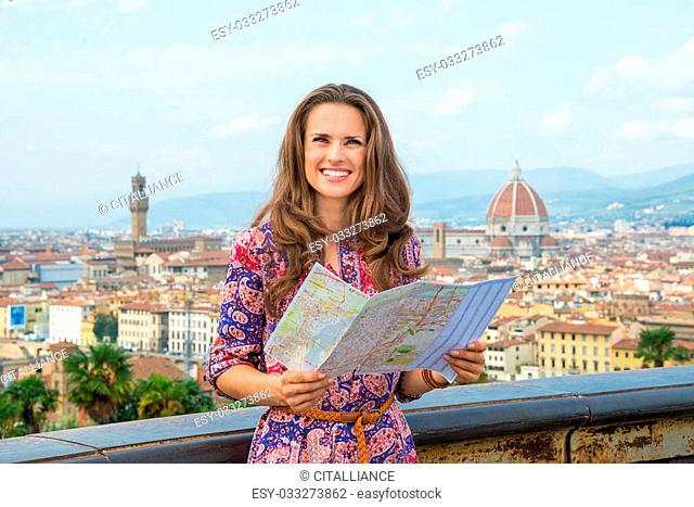 Happy young woman with map against panoramic view of florence, italy