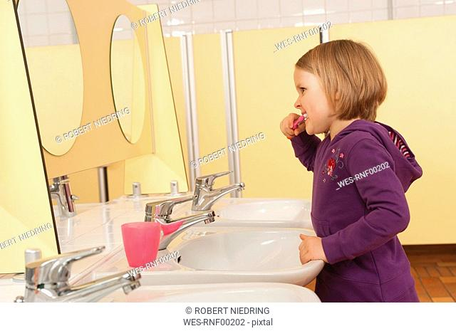 Germany, Gril 3-4 standing in front of mirror, brushing her teeth, side view, portrait