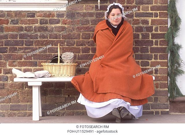 Colonial Williamsburg, Virginia, VA, Williamsburg, A woman interpreter dressed in a colonial costume sits outside the Courthouse in Colonial Williamsburg