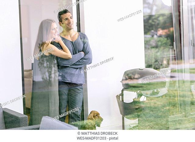 Smiling couple with dog standing at terrace door