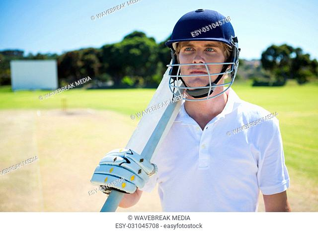 Thoughtful cricket player holding bat while wearing helmet