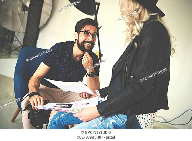 Photographer and stylist having discussion in photography studio