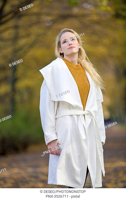 Pensive pretty blonde woman with coat in Park in Autumn
