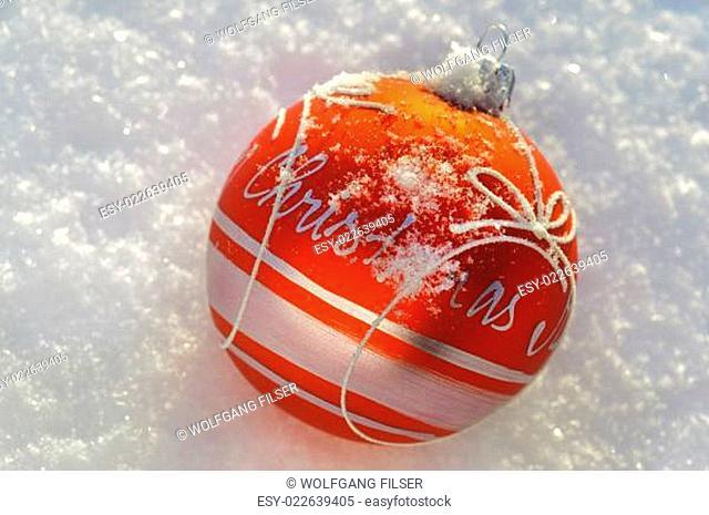 Rote Christbaumkugel liegt im Schnee
