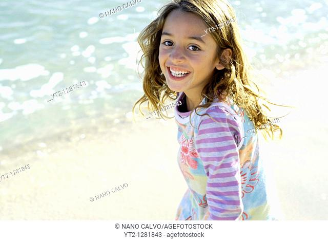 Cute seven year old brazilian girl, playing on the beach of Santa Eulalia del Rio, Ibiza, Spain, during a beautiful and sunny day