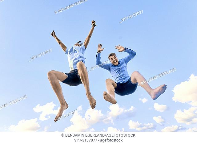 Two male friends jumping against sky