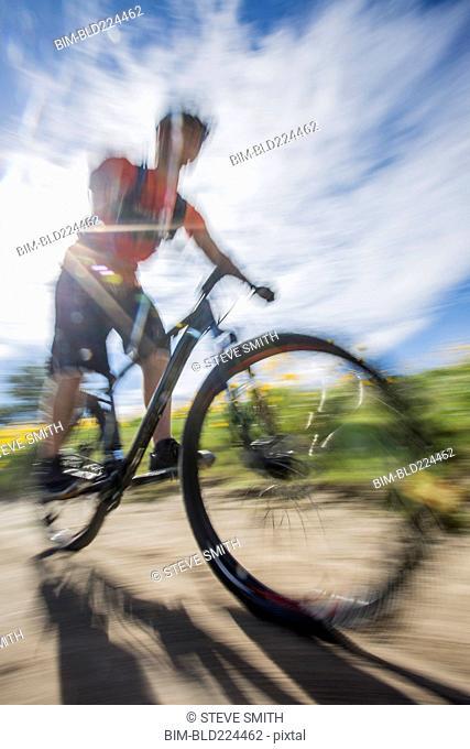 Blurred view of man riding mountain bike