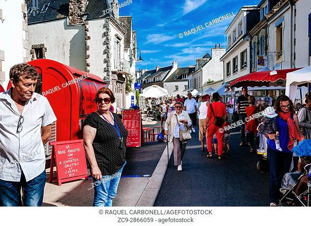 People walking through market stalls in a crowded street. Carnac, Brittany, France
