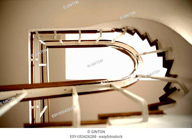 The underview of a staircase with a spiral staircase and railings