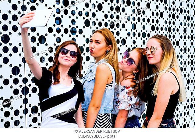 Friends taking selfie with digital tablet, screen in background