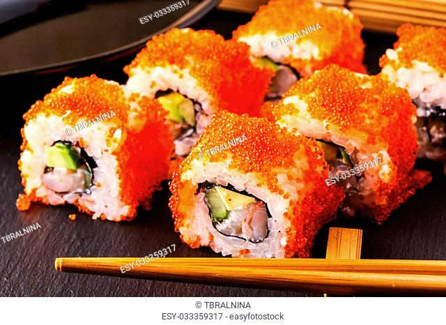 Sushi roll with crab, avocado, cucumber and tobiko, selective focus