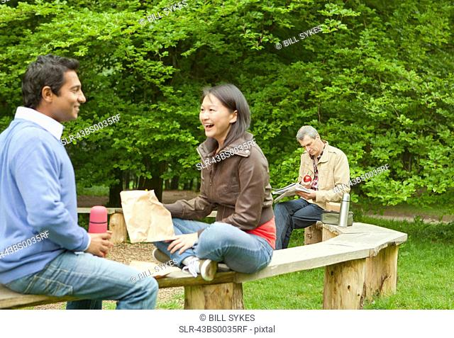 Couple talking on wooden bench in park