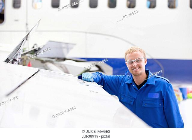 Portrait of smiling engineer leaning on wing of passenger jet in hangar