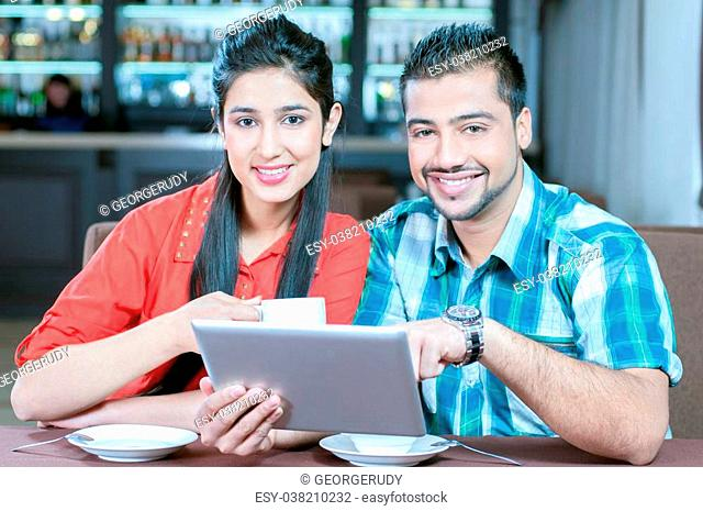 Asian woman and man are sitting in a bar or cafe and are surfing the internet with a tablet computer