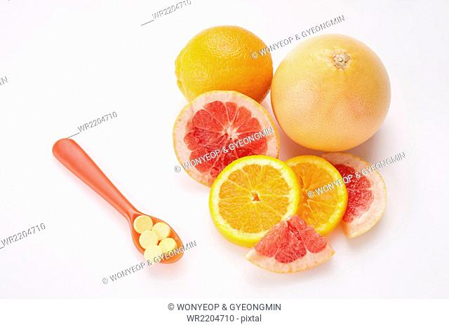 High angle of a spoon of vitamin pills and slices of orange and grapefruit with a whole fresh orange and whole grapefruit