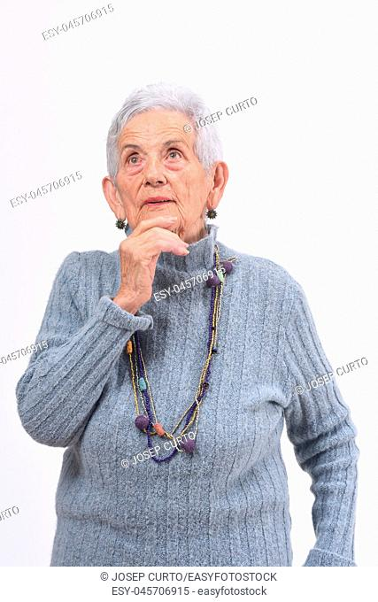 thoughtful senior woman looking up on a white background