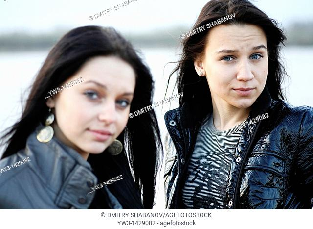 two beautiful brunette outdoor portrait near water sea, river or pond