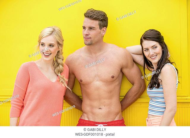 Portrait of man in trunks between two women in front of yellow background