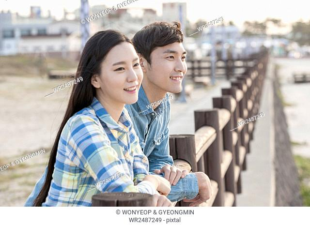 Side view portrait of young smiling couple leaning at fence in Jeju, Korea