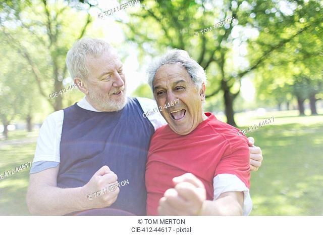 Exuberant active senior men friends cheering in park