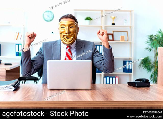 The businessman wearing mask in hypocrisy concept