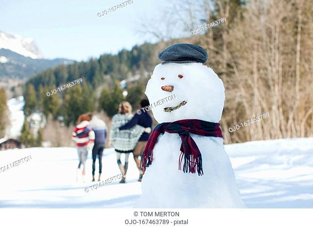 Snowman, people walking in background