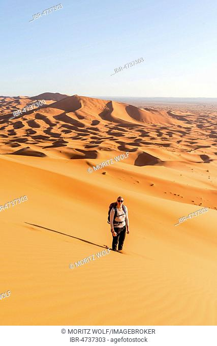 Woman stands in the sand on dune, red sand dunes in the desert, dune landscape Erg Chebbi, Merzouga, Sahara, Morocco