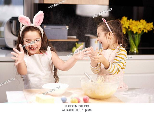 Two playful sisters having fun baking Easter cookies in kitchen together