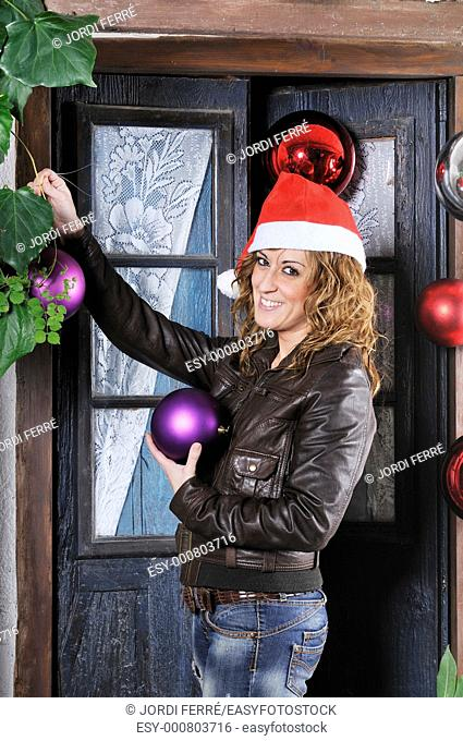 Young woman decorates with christmas balls a door