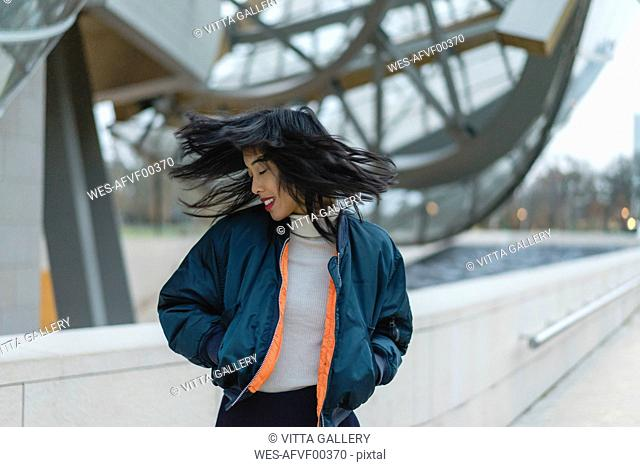 France, Paris, smiling young woman tossing her hair