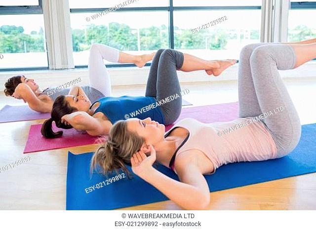 Women doing core exercise on mats in fitness studio