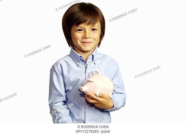 Young boy holding ceramic piggy bank; Montreal, Quebec, Canada