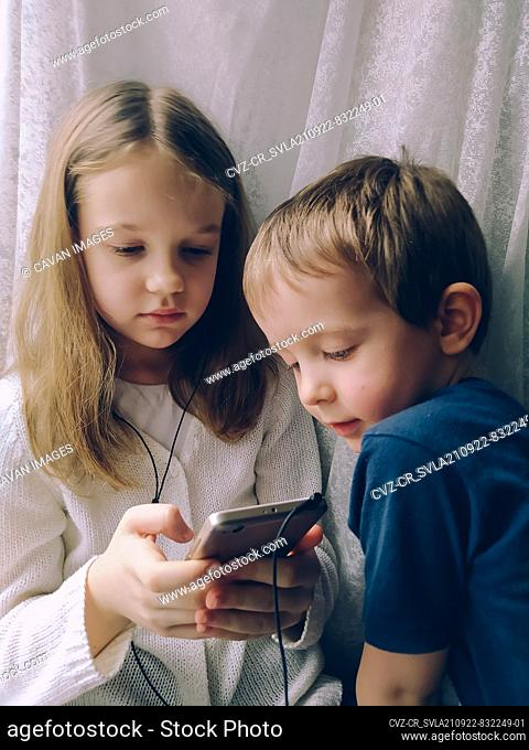 Little boy and girl at home with phone and headphones at home