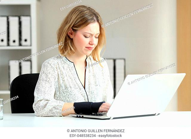 Handicapped office worker working online writing in a laptop and suffering wrist ache