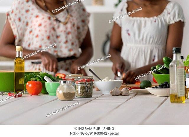 Two unrecognizable african women cooking in kitchen making healthy food salad with vegetables