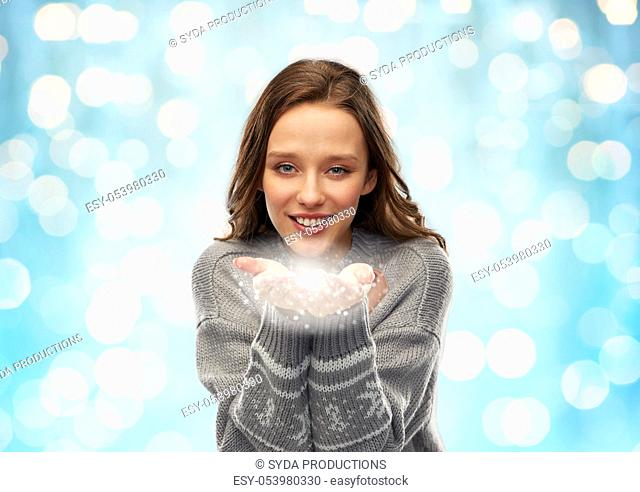 young woman in christmas sweater with fairy dust