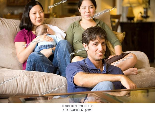 Portrait of an Asian-Caucasian family sitting on sofa and the floor