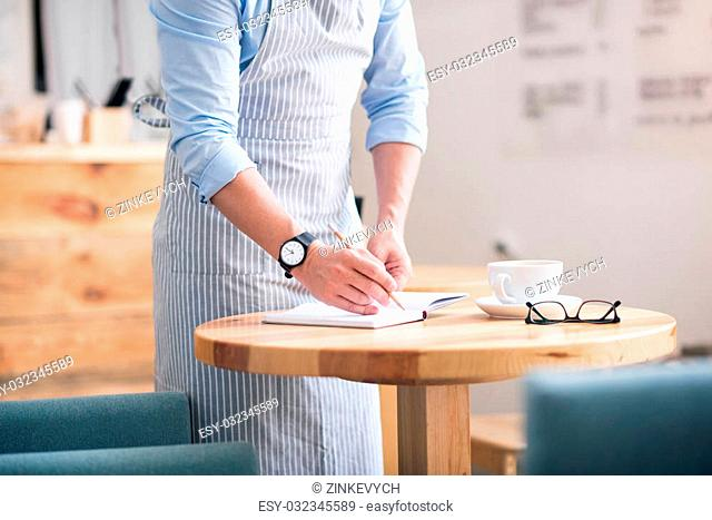 Opening own business. Cropped picture of man wearing apron making some notes