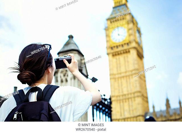 Young Japanese woman enjoying a day out in London, taking a picture of Big Ben