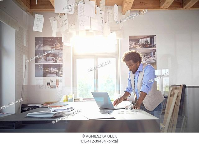 Male graphic designer working at laptop in office