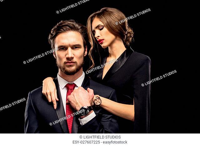 Portrait of beautiful sensual couple hugging and flirting on black