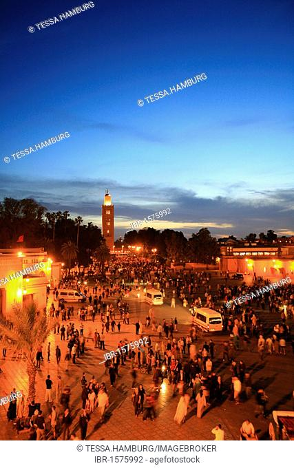Koutoubia Mosque illuminated with red light, Djemaa el-Fna Square of the Hanged Man in the medina quarter of Marrakech at dusk with its countless food stalls
