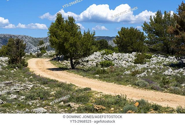 Dusty track atop of Mount Srd heads off into the mountains, Croatia, Europe