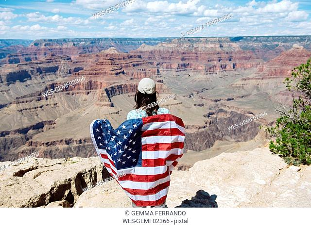 USA, Arizona, smiling woman with American flag at Grand Canyon National Park, rear view