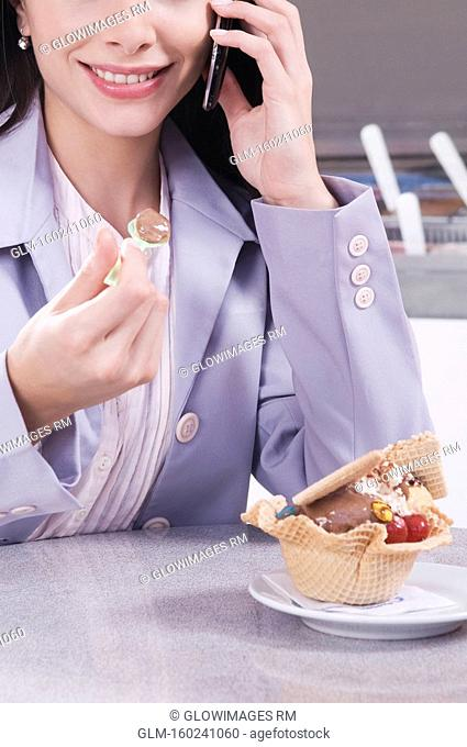 Woman eating ice cream and talking on a mobile phone