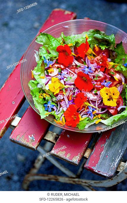 Colourful salad with edible flowers in a bowl on a garden chair