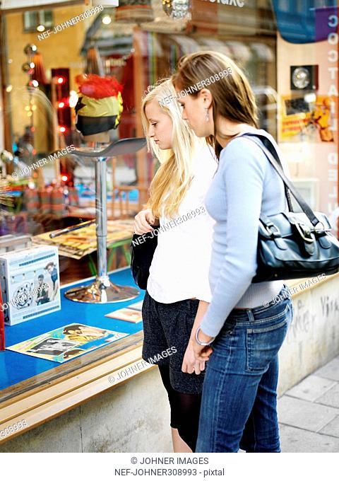 Two teenage girls looking in a shop-window