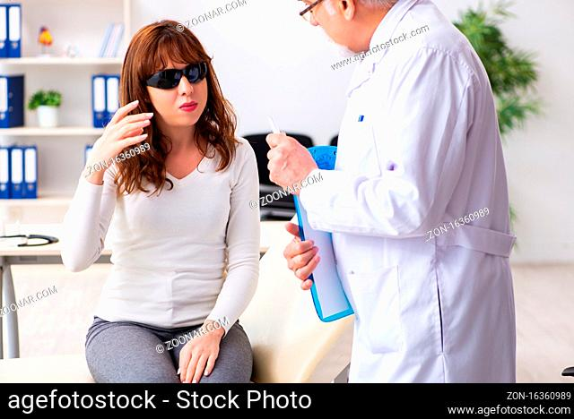 Young woman visiting male doctor ophthalmologist